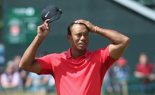Tiger Woods looks upset as his rubs his head.