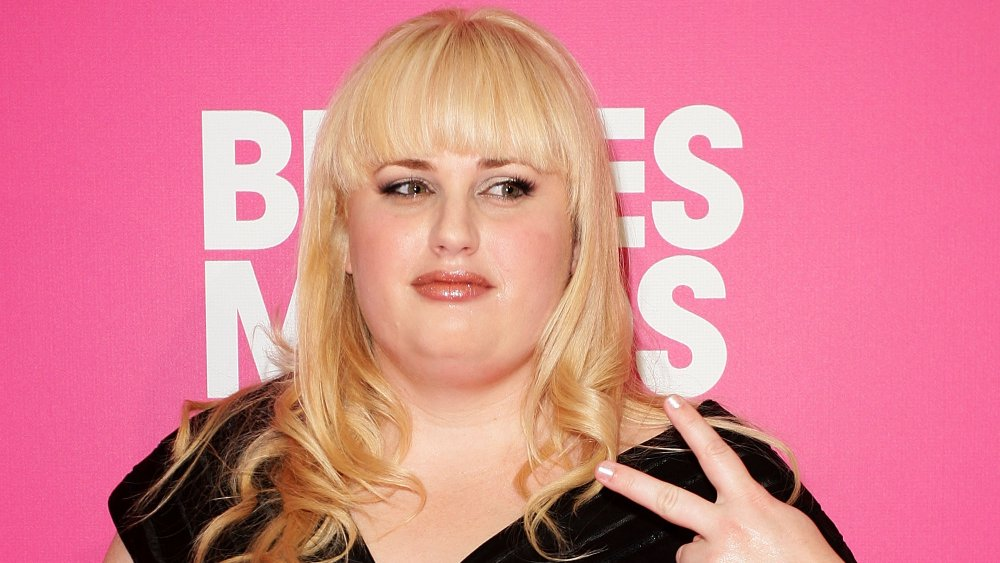 Rebel Wilson flashing a peace sign at the Bridesmaids premiere