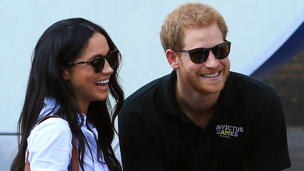 Meghan Markle and Prince Harry, both in sunglasses