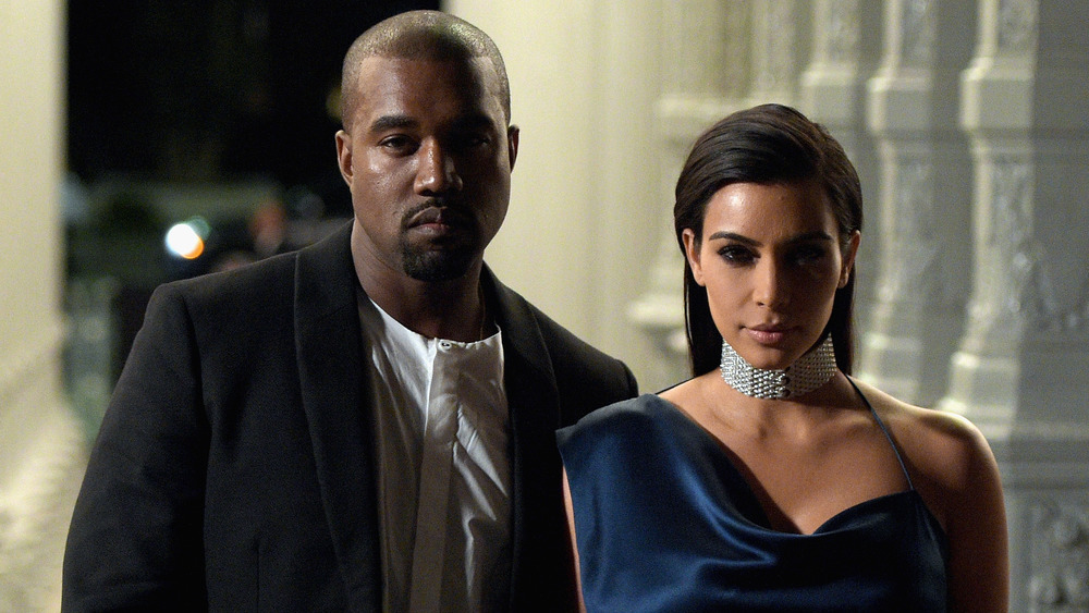 Kanye West and Kim Kardashiain standing in shadows
