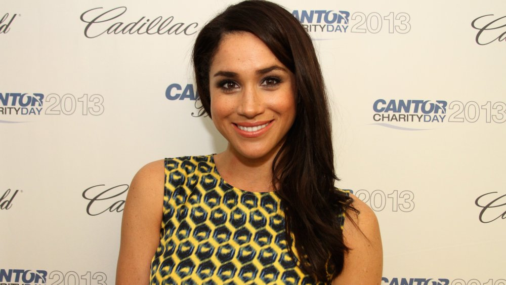 Meghan Markle in a black and yellow printed dress