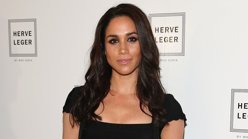 Meghan Markle in front of a Herve Leger wall