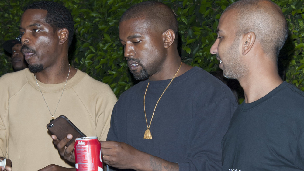 Kanye West looking at a phone