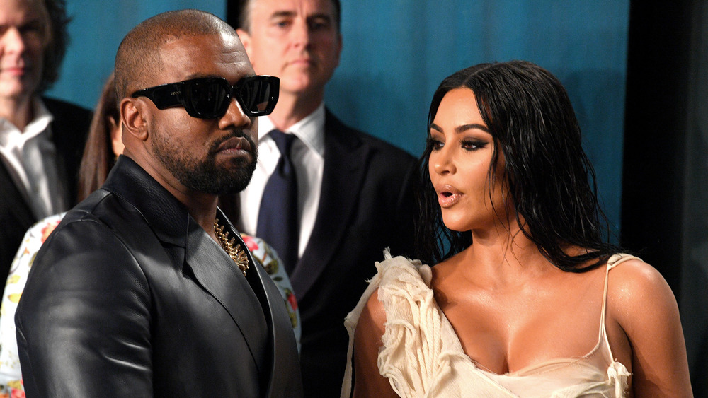 Kanye West in sunglasses with Kim Kardashian sporting wet-look hair