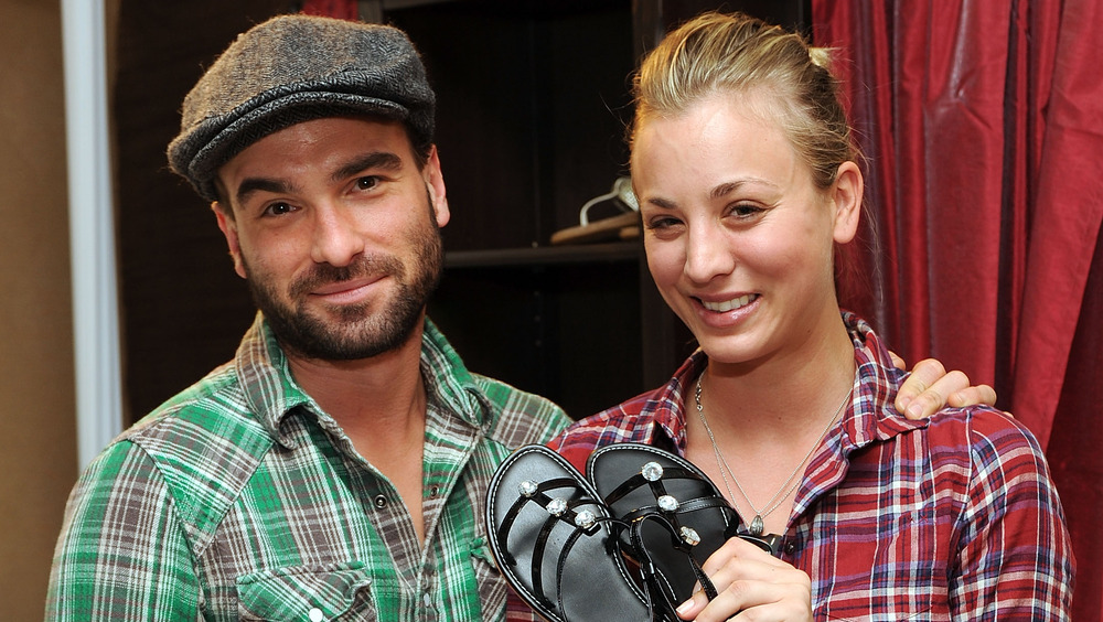 Kaley Cuoco holding up shoes beside Johnny Galecki