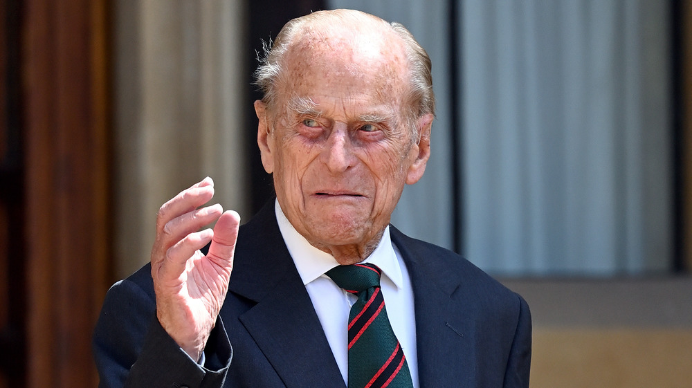 Prince Philip waving with a grimace