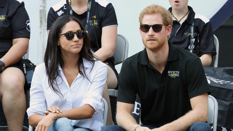 Meghan Markle Prince Harry seated and wearing sunglasses